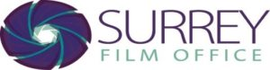 Surrey Film Office logo. Surrey Film Office text in purple and blue with a purple film lense graphic on the left