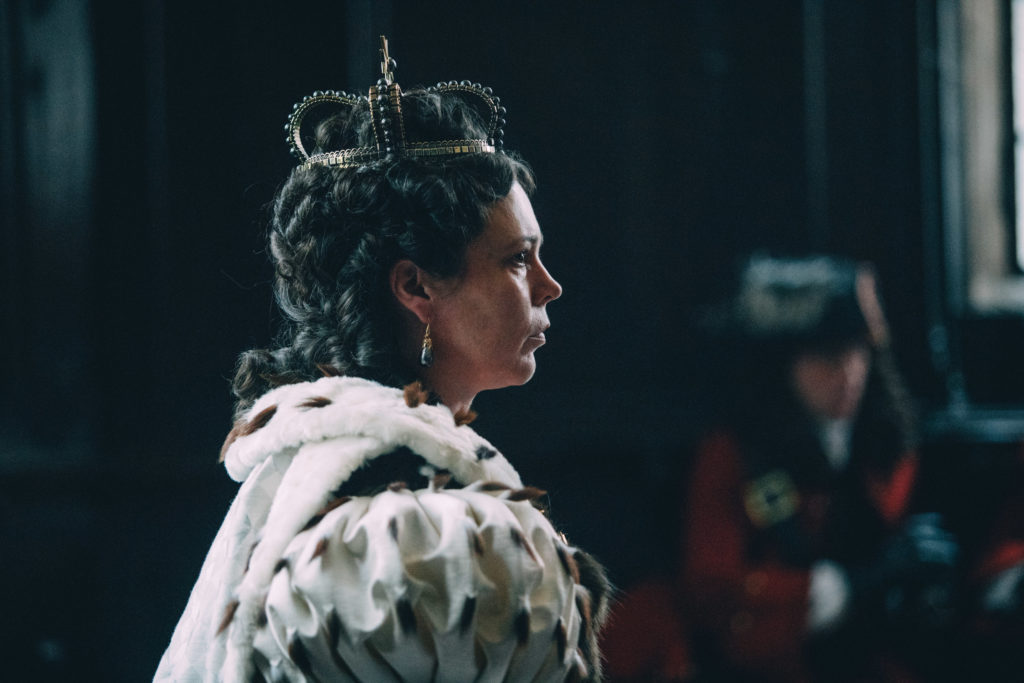 Olivia Colman as Queen Anne in The Favourite. Side view of Olivia wearing a cloak and crown staring into the distance.