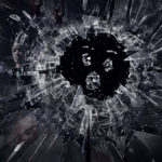 Series Poster for Black Mirror, picturing a broken mirror with a small face within the broken pieces of mirror