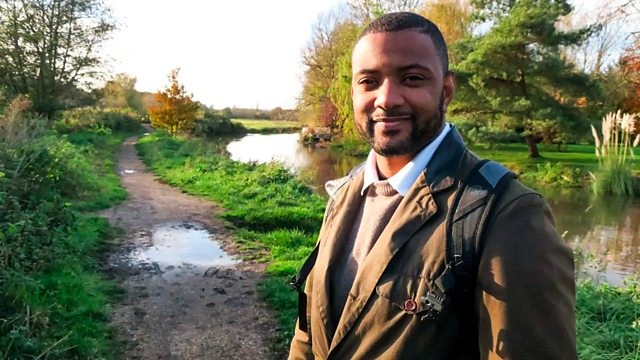 Presenter JB Gill pictured weaiting a brown jumper and jacket in the countryside with greenery behind him as he walks along the river
