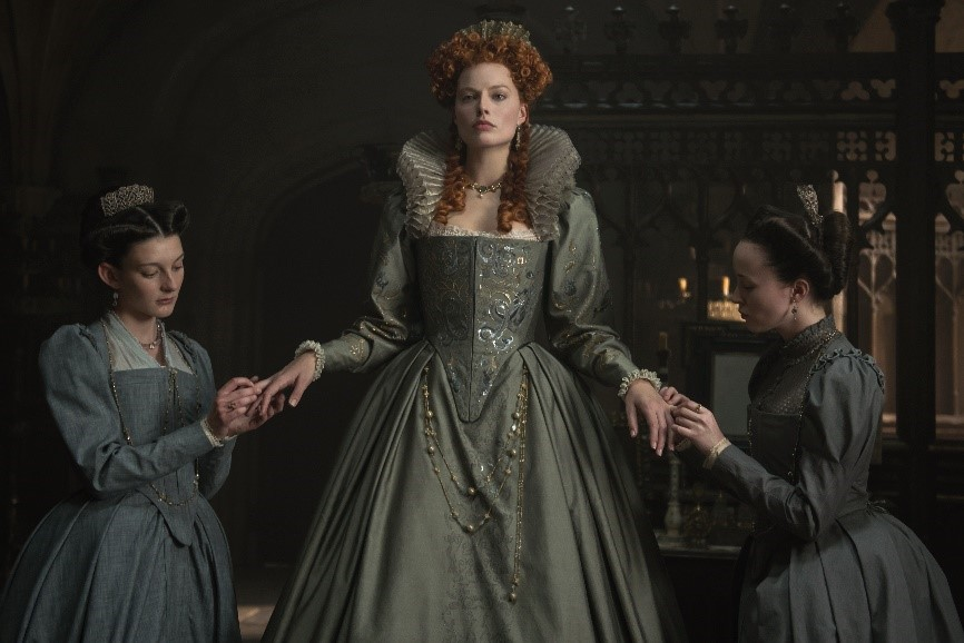 Margot Robbie in Mary Queen of Scots seen standing in the dark in a long grey dress, with a maid at each side dressed in the same grey colour.
