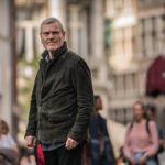Actor Tchéky Karyo starring as investigator Julien Baptiste wearing a brown jacket pictured standing in a street looking around with people blurred behind him.