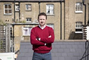 Presenter Matt Allwright for BBC One's The Empty Housing Scandal standing in front of some brown houses wearing a red jumper with his arms crossed.