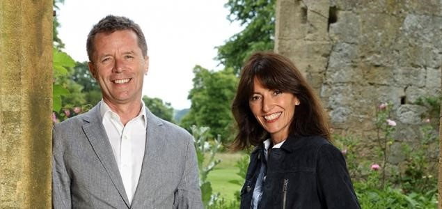 Presenters Davina McCall and Nicky Campbell pictured standing together smiling at the camera in front of an historic wall. Davina is wearing a denim jacket and nicky has a grey suit on.