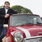 James Martin pictured in a black jumper standing next to a red mini car as he leans on it. Grass and trees are in the background.