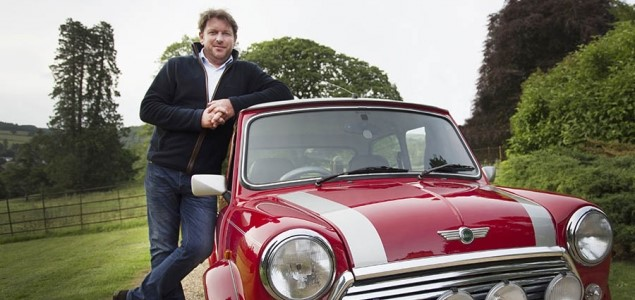 James Martin pictured standing next to a red car as he leans on it