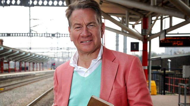 Image of presenter Michael Portillo at one of Britain's railway stations wearing a blue jumper and pink blazor. Tracks and the station can be seen in the background.