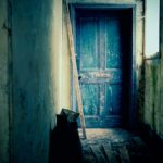 Series poster for The Empty Housing Scandal - an image of a blue door in a run-down looking house
