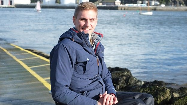 Presenter Steve Brown pictured in a blue coat sitting in his wheelchair by the seafront. Sea, road and boats can be seen in the background.