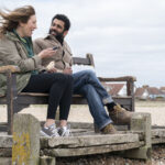 Daisy Haggard as Miri Matteson is sat on a bench on a pebbled beach with Adeel Akhtar as Billy. She has long hair blowing in the wind and is holding her phone and a sandwich. She is wearing a green anorak and black leggings. Adeel has black hair and a beard and wears a brown jacket and blue jeans.