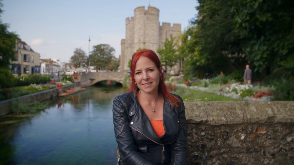 Presenter Alice Roberts sitting by the river in Canterbury.