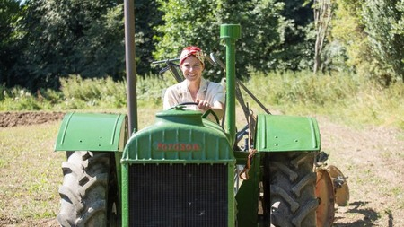 Presenter Alice Roberts wearing a pink top and headband seen driving a green tractor in a field in Dover, Kent.