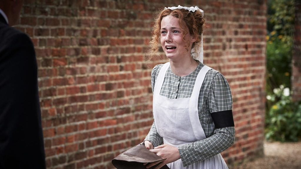 Isabel Clifton is dressed in a victorian maid's costume as character Hetty Feather stood near a brick wall