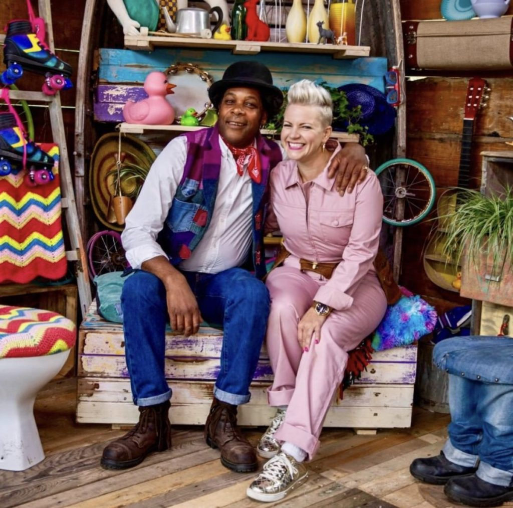 Presenters Zoe Pocock (wearing a pink jumpsuit) and Danny Sebastian (wearing a patchwork waistcoat and jeans) in Junk Rescue pictured sitting down together on a wooden box and smiling at the camera.