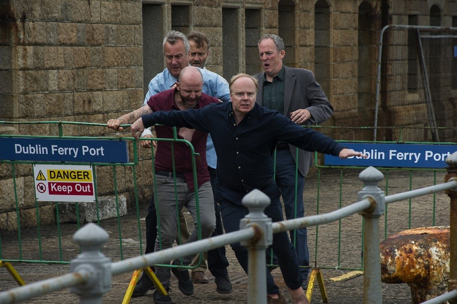 Jason Watkins and his four other cast members wearing shirts seen running and struggling through Dublin Ferry Port barriers on a cobbled street.