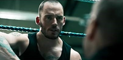 Liam (Sam Claflin) pictured wearing a black vest in a boxing ring, talking to someone who's face we don't see as their back is to us.