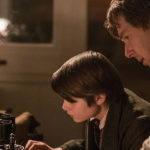 Benedict Cumberbatch as Thomas Edison, leaning over the shoulder of a child and teaching them by a desk.