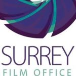Surrey Film Office logo- Purple and blue text reading Surrey Film Office with half of a purple camera lense on top. Links to their website.