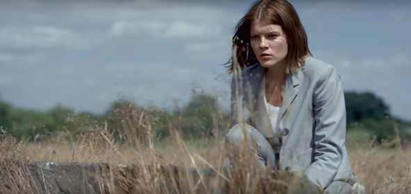 Emma Greenwell in The Rook bending down in a field, looking down at the ground.