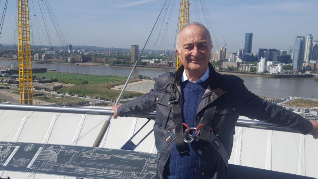 Tony Robinson smiling at the camera, with a view of the Thames river in the background below.