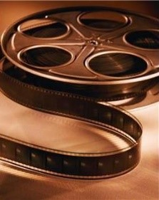 Sepia image of a film reel unravelling towards the camera