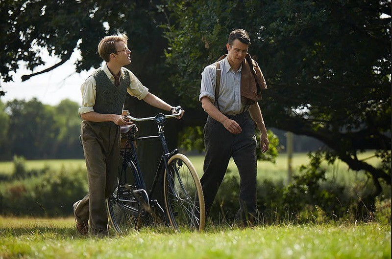 Two young men walking through a field talking to each other. Both wearing period clothing and the one on the left is walking with his bike.