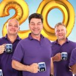 Image of four of the team featuring in the Big Build Anniversary Special, standing with mugs of tea in their hand and a big '20' balloon behind them.