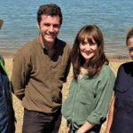 Dr Tori Herridge and his team of three smiling at the camera standing on the beach with the sea in the background.