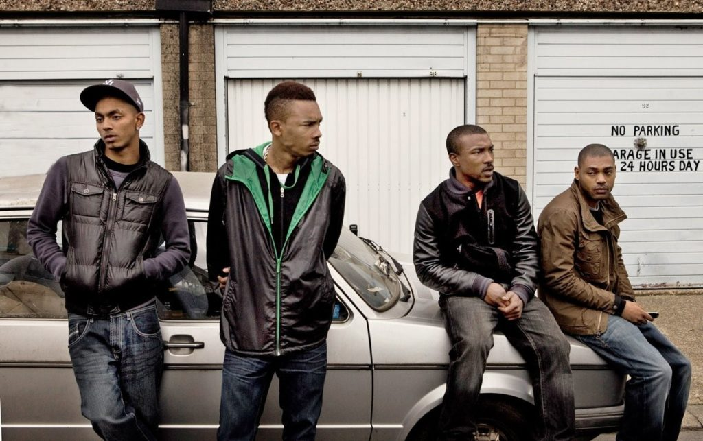 Group of four men, two sitting and two leaning against a grey parked car in front of a block of garages. All men wearing jackets and jeans.