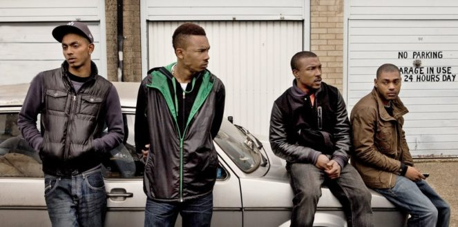 Group of four men, with some sitting and some leaning on a grey car parked in a street.