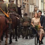 Actor Jonah Hauer wearing a grey suit riding a bike with Zofia Wichlacz wearing a pink top and skirt sat in front of him. Cycling along a cobbled street with an army parade with horses behind them.