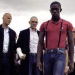 Image of young Nigerian man (leader) standing outside, with his white skinhead gang standing behind him.