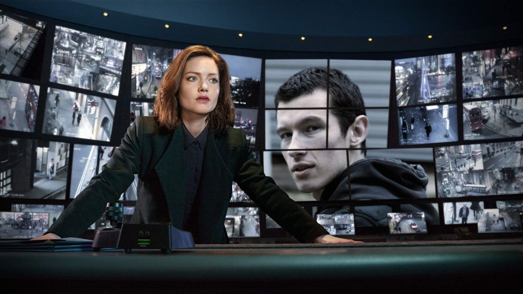A female detective wearing a suit standing at a desk with big screens behind her showing a fugitive and CCTV footage.