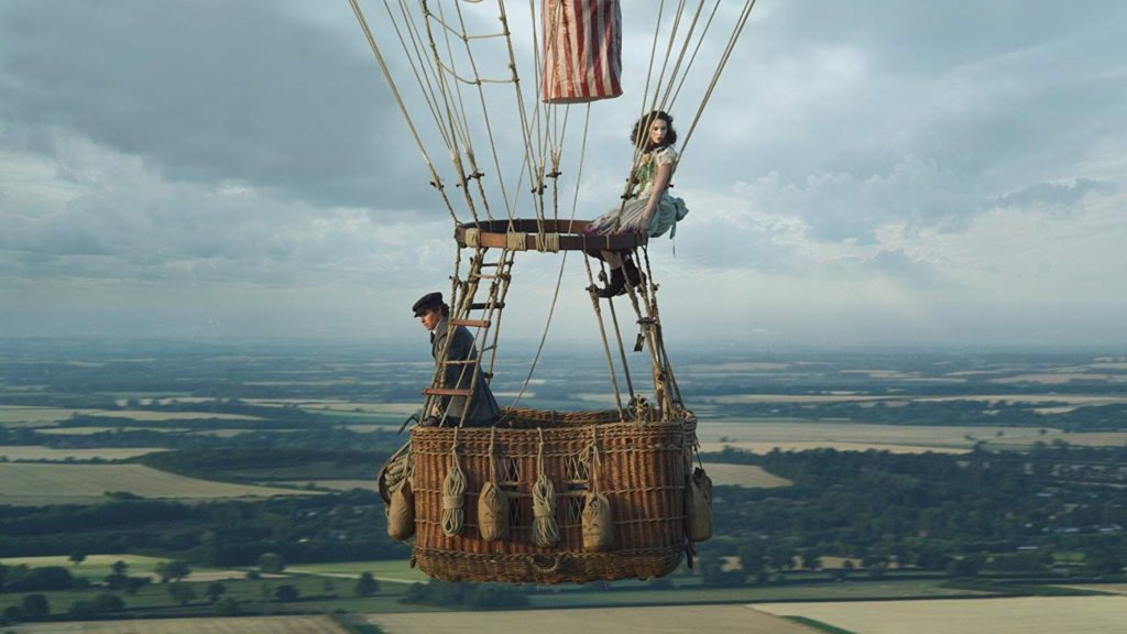 A man standing in a hot air balloon looking over the countryside with a women sitting high up on the edge of the balloon looking out into the distance.