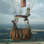 A man and woman sitting in a hot air balloon.
