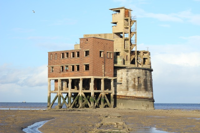 Grain Battery Tower a semi derelict martello tower on an estuary with sea in the background.
