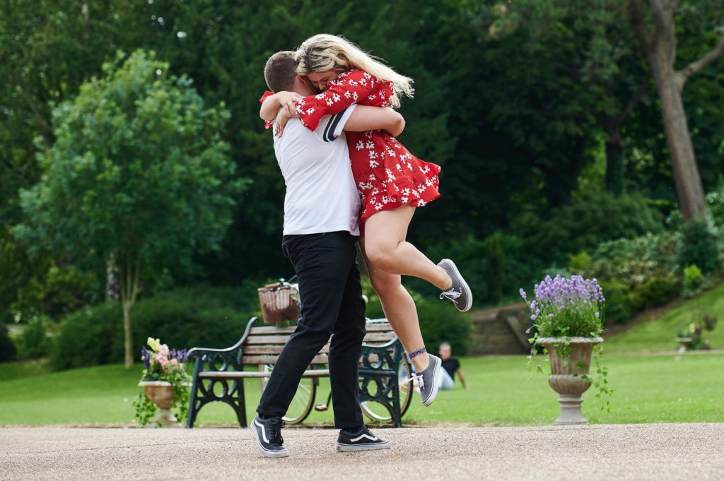 Pictured are Kerry in a red dress and Jordan in a white top embracing by a bench in a park.
