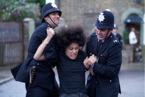 A woman is struggling with two policeman stood either side of her holding her arms. They are outside a building.
