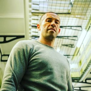 A scarred man wearing a grey jumper looks down at the camera. Above him is prison railings