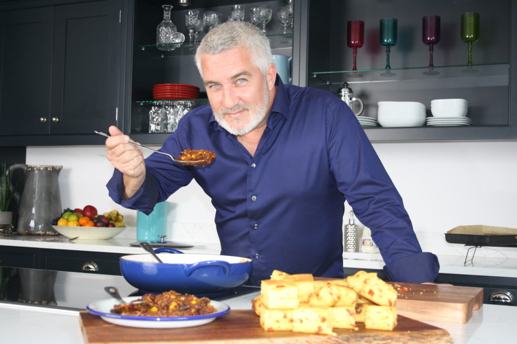 Paul Hollywood posing in a blue shirt with a spoonful of food in a kitchen, behind a counter full of full.