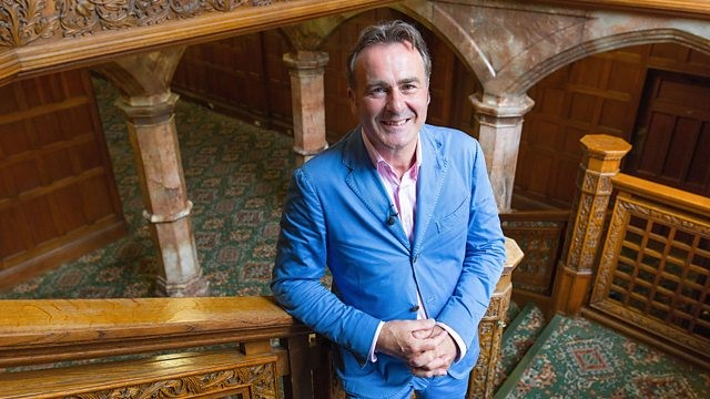 Presenter Paul Martin wear a blue suit and stands leaning on a wooden banister of a staircase