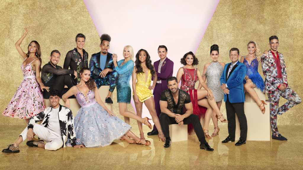 15 celebrity contestants dressed in their ballroom outfits, posed in a row smiling at the camera in front of a gold background.