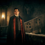 CLAES BANG as Dracula wearing a cape and looking into the camera in candle light . An old stone staircase can be seen behind him.