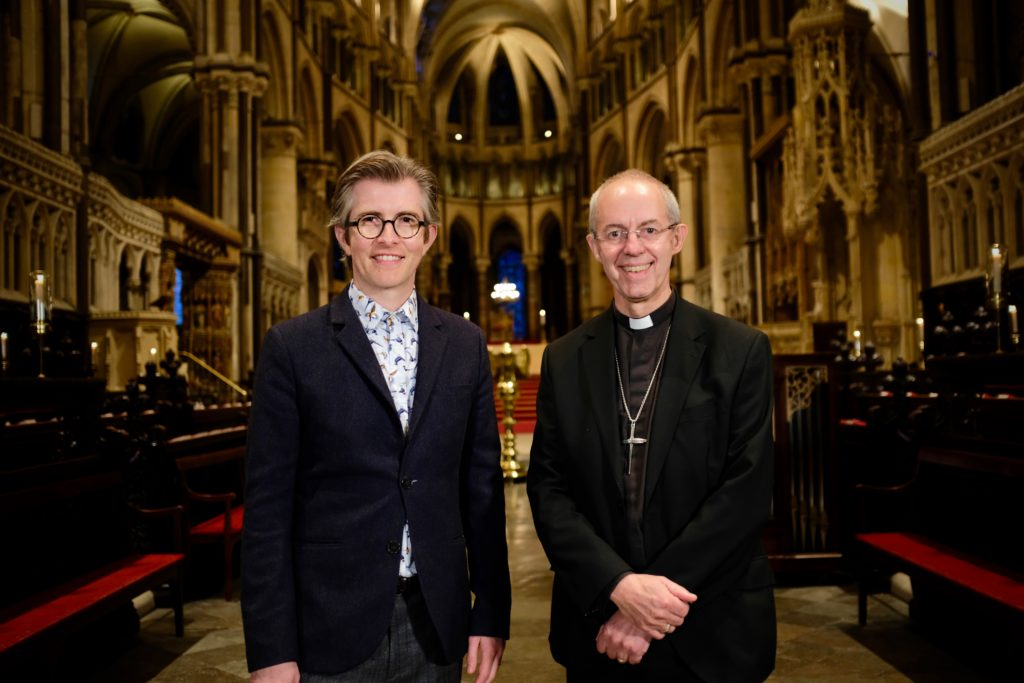 A man in a suit and a vicar stand in front of the altar in the cathedral