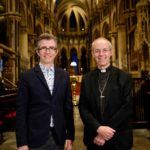 Gareth Malone wearing a suit and the Archbishop of Canterbury smiling at the camera inside the cathedral.