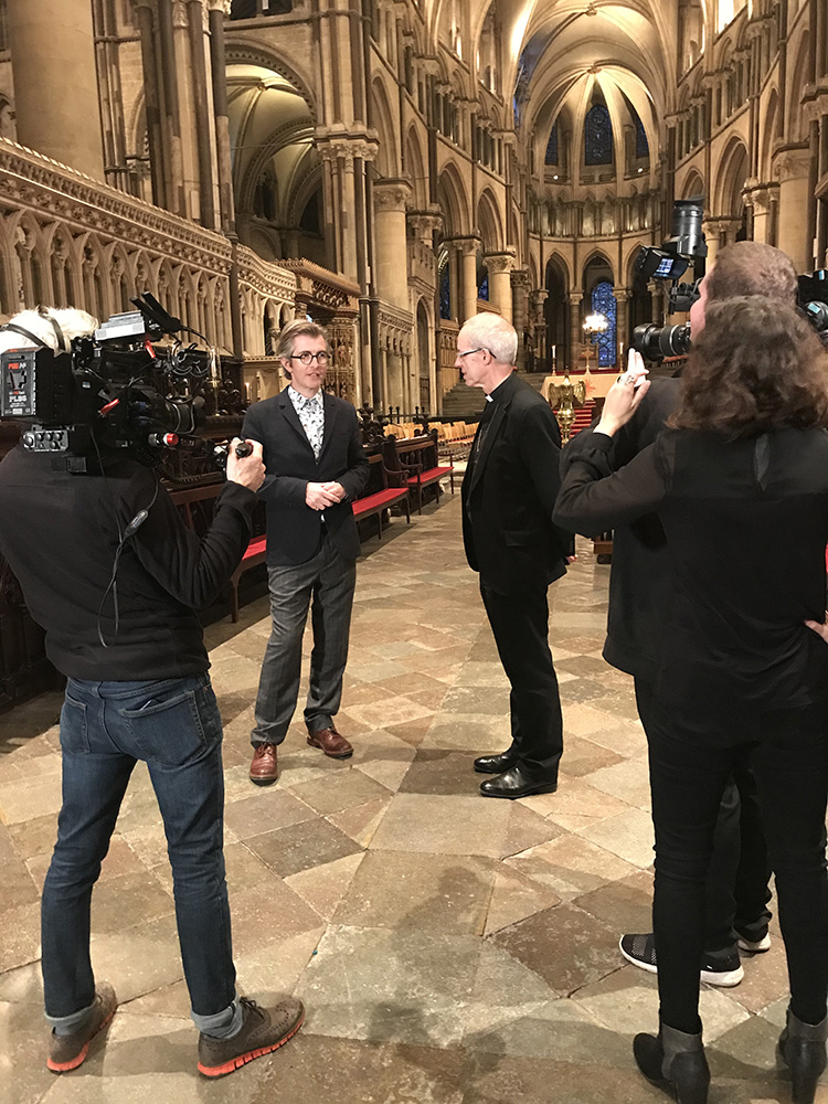 A camera crew film two men inside a cathedral