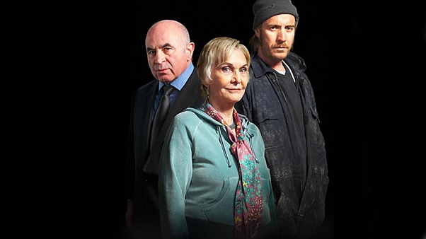 Three cast members standing posing for the camera against a black background. The women in the centre is wearing a blue jumper, the men either side of her are wearing dark clothes.