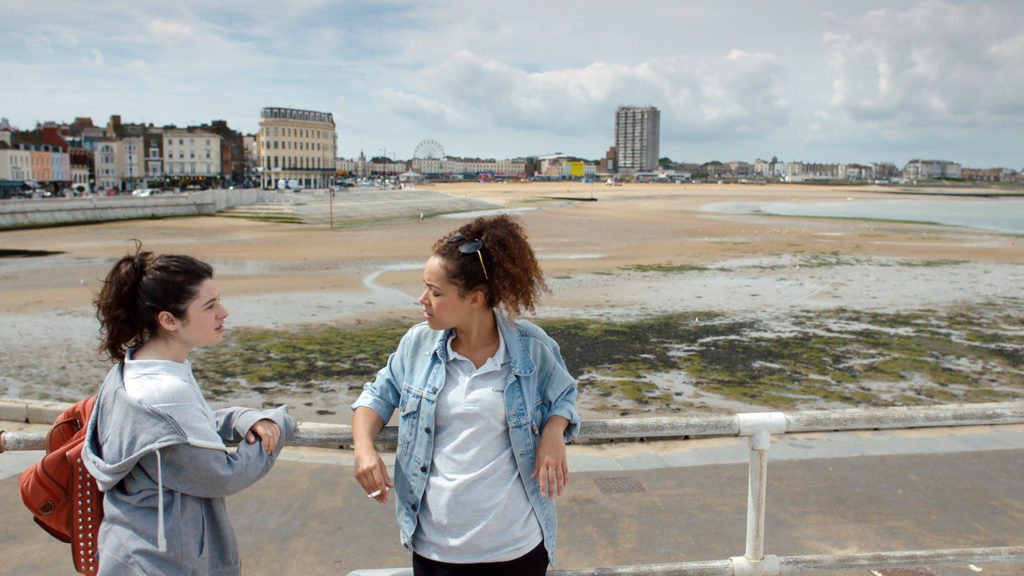 Two characters wearing casual clothes standing and talking in front of Margate beach leant against the railing.