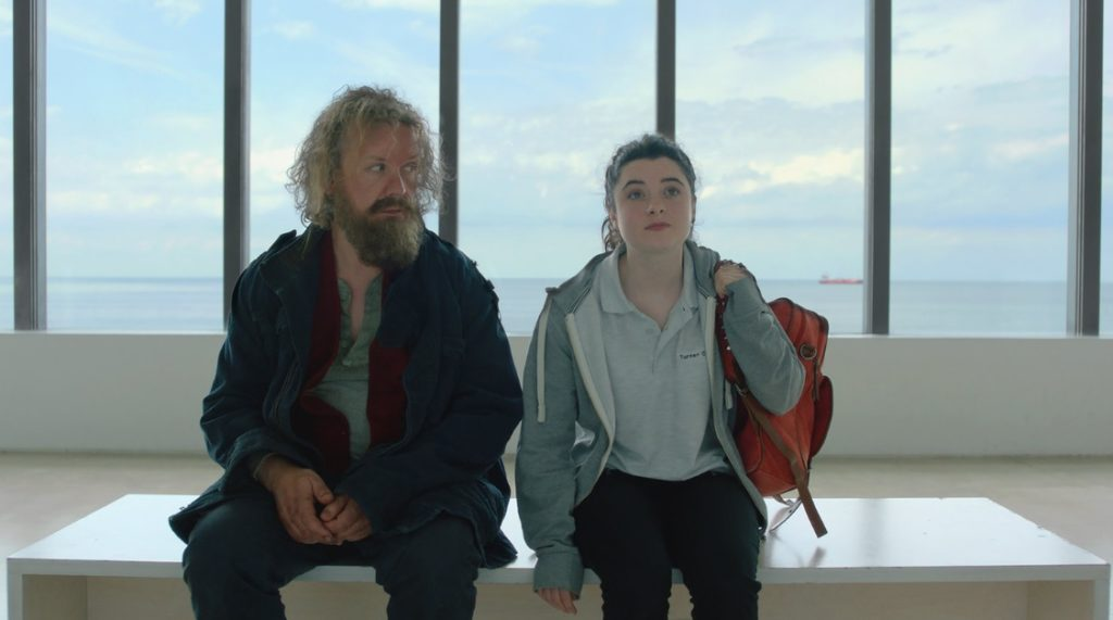 Two characters sitting on a white bench in front of a white wall and window at the Turner Contemporary Gallery. Sea can be seen through the window.