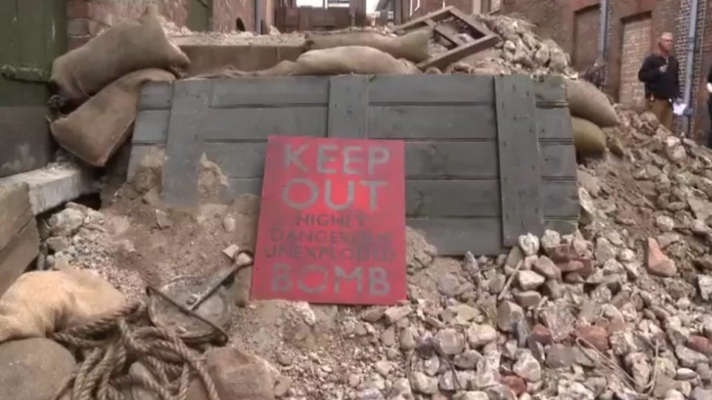 An image of an exploded bomb set, a pile of rubble and a sign saying KEEP OFF